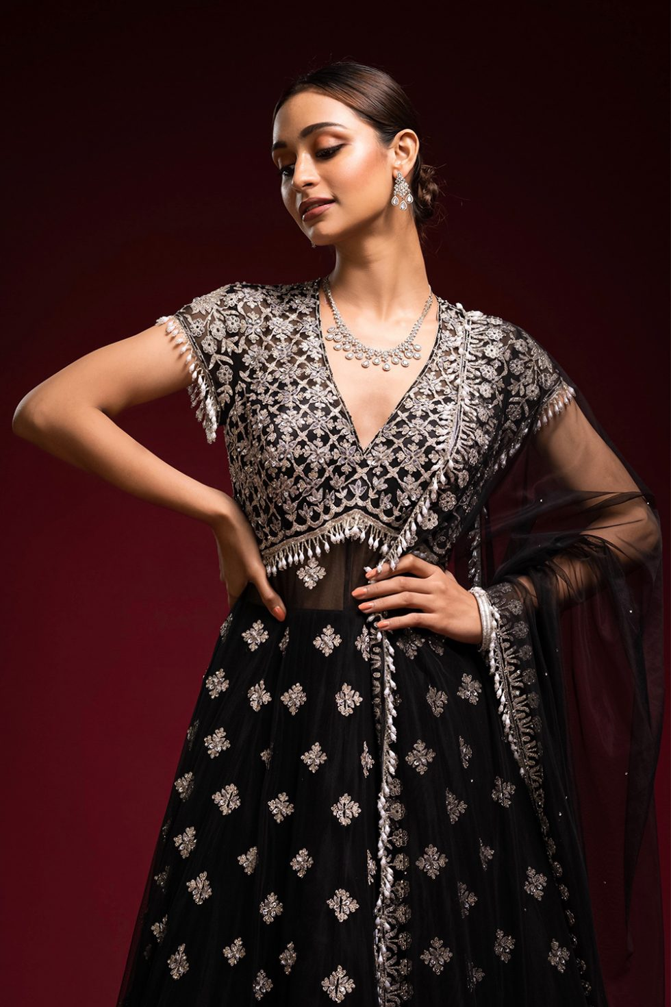 Raven black gown set with silver embroidery paired with a matching dupatta, silver embellishments and pearl tassels.