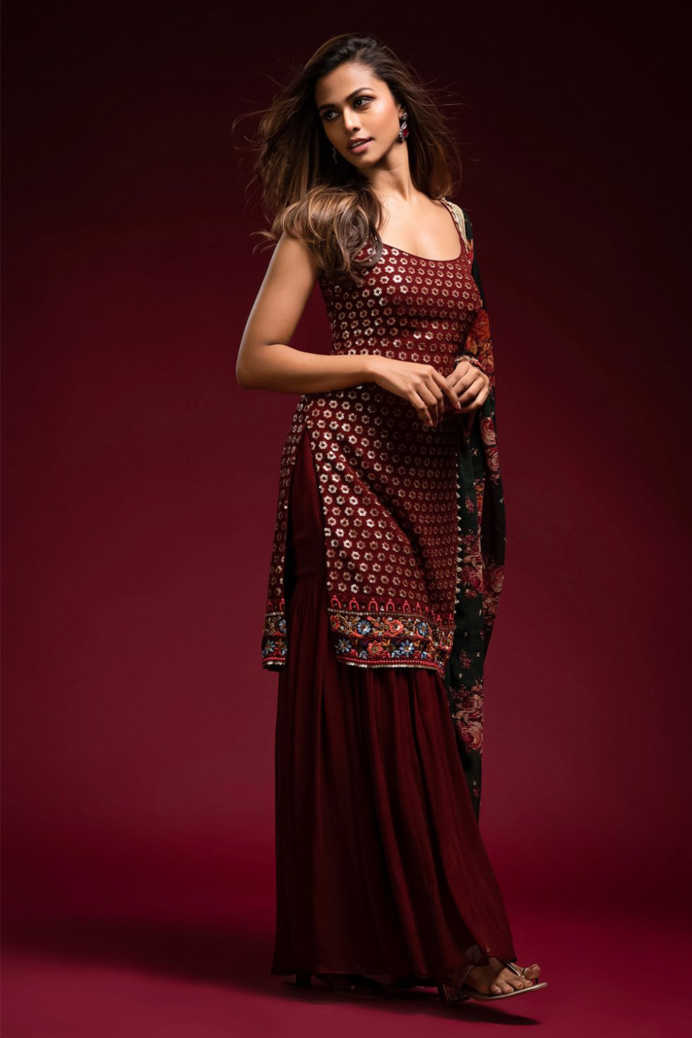 Deep maroon single tiered sharara pant set with a long chikan kurta top paired with a contrast printed dupatta and gold embellishments.