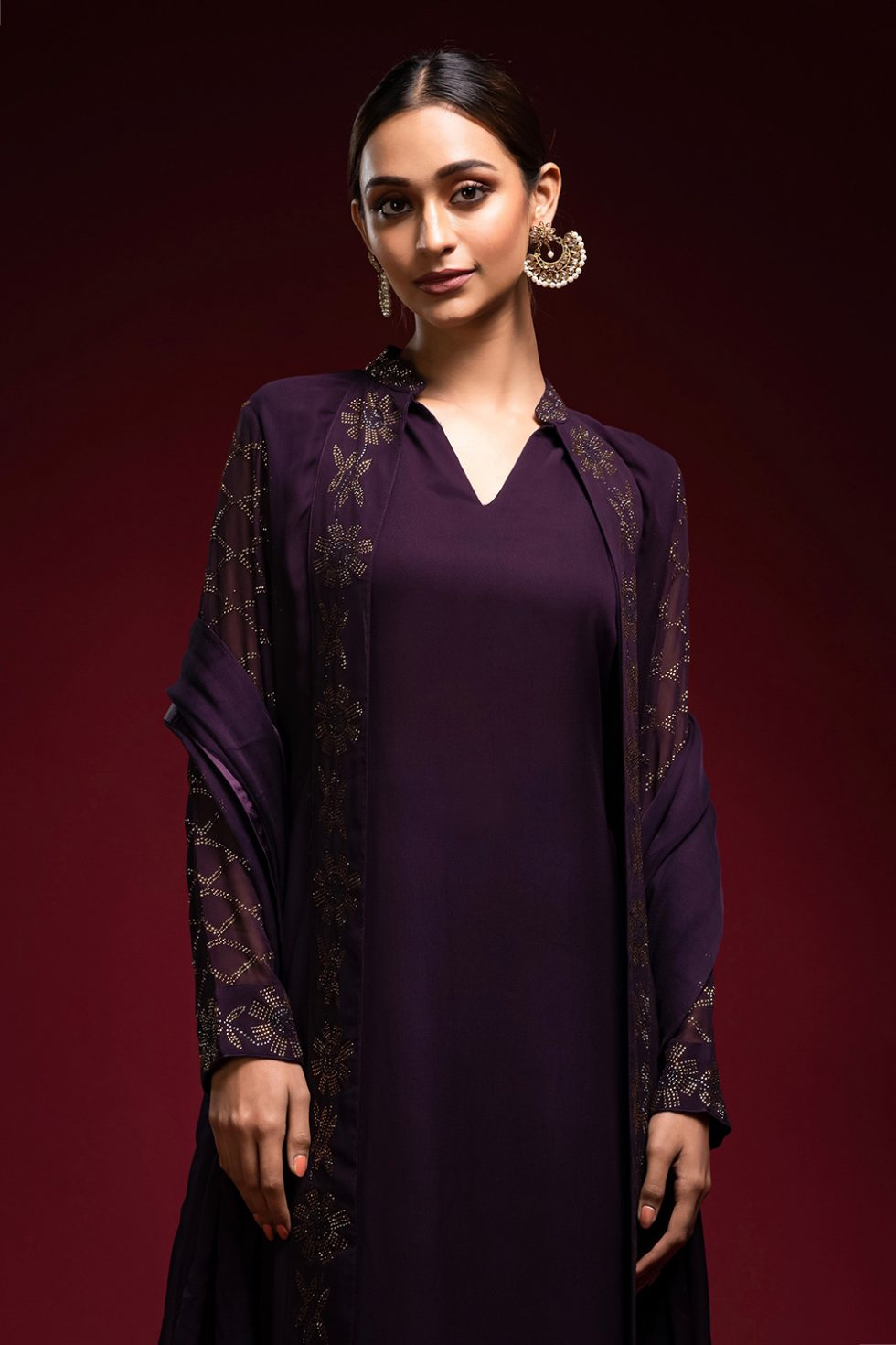 Deep purple salwar set with a self coloured churidar paired with a matching jacket with gold embellishments and a dupatta.