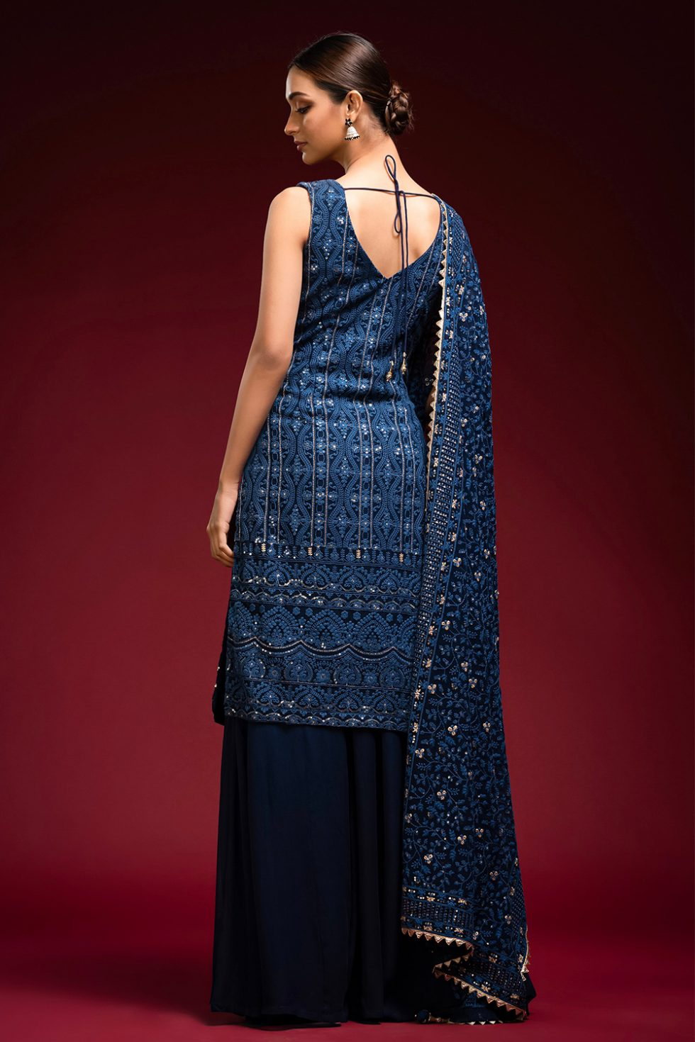 Deep blue palazzo pant set with an overlap style long chikan kurta top paired with a matching chikan dupatta and gold embellishments.