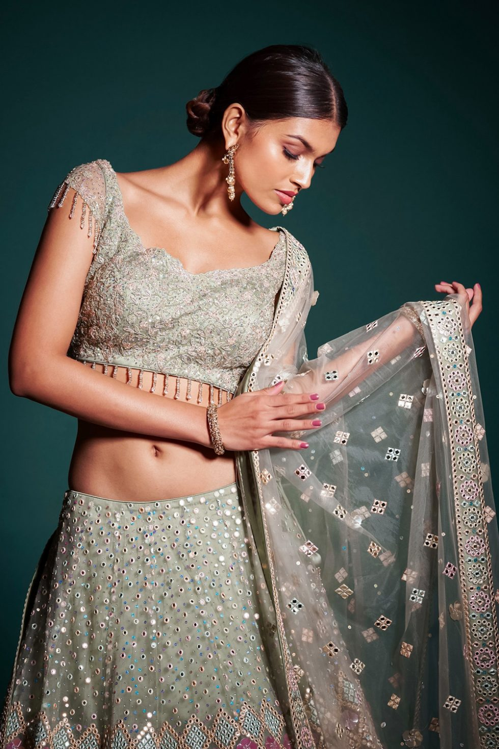 """Ash green lehenga set with multi coloured embroidery and """"abla"""" paired with a matching dupatta and tassels."""
