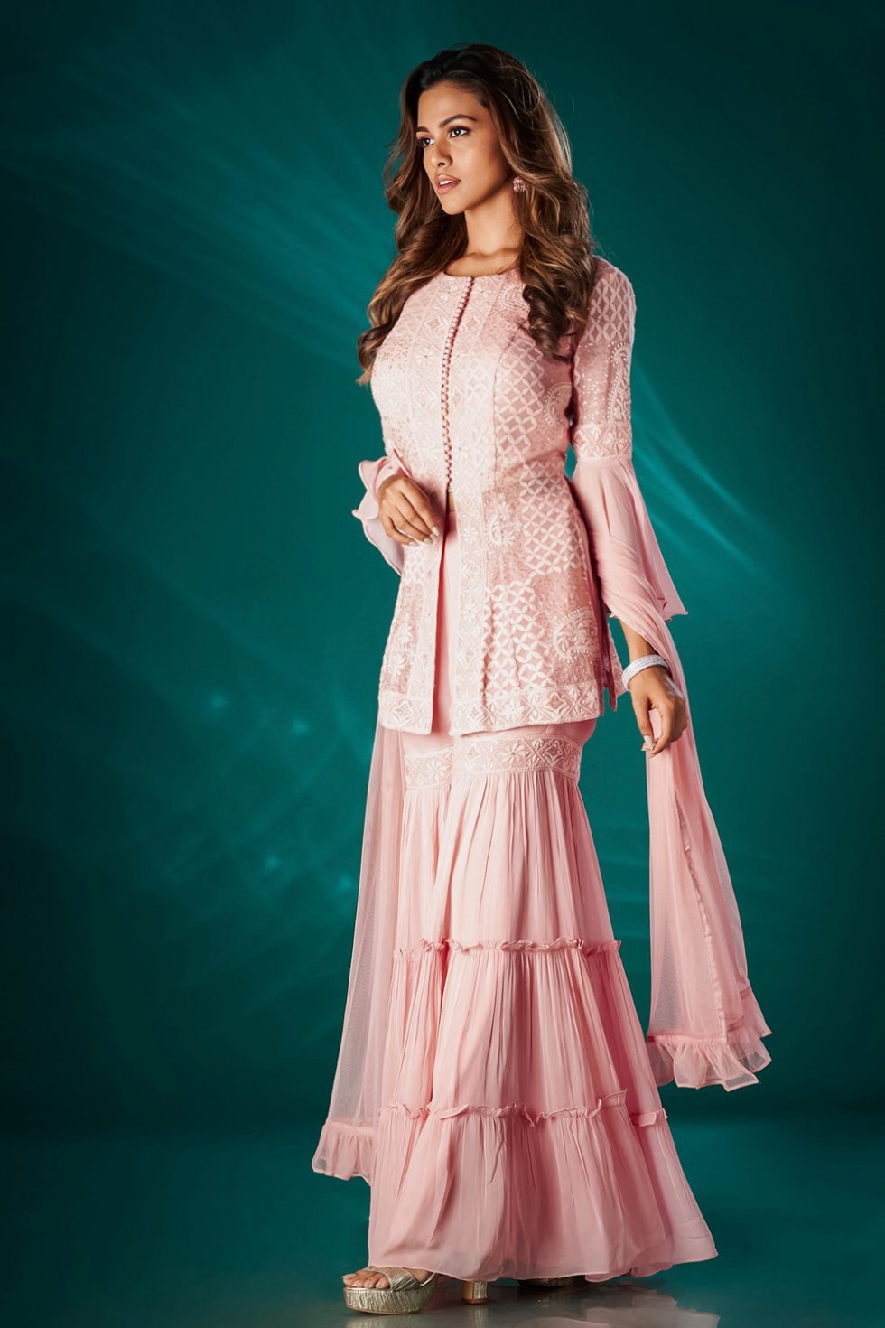 Petal pink tiered sharara pant set with a chikan jacket style top with bell sleeves paired with a matching dupatta.