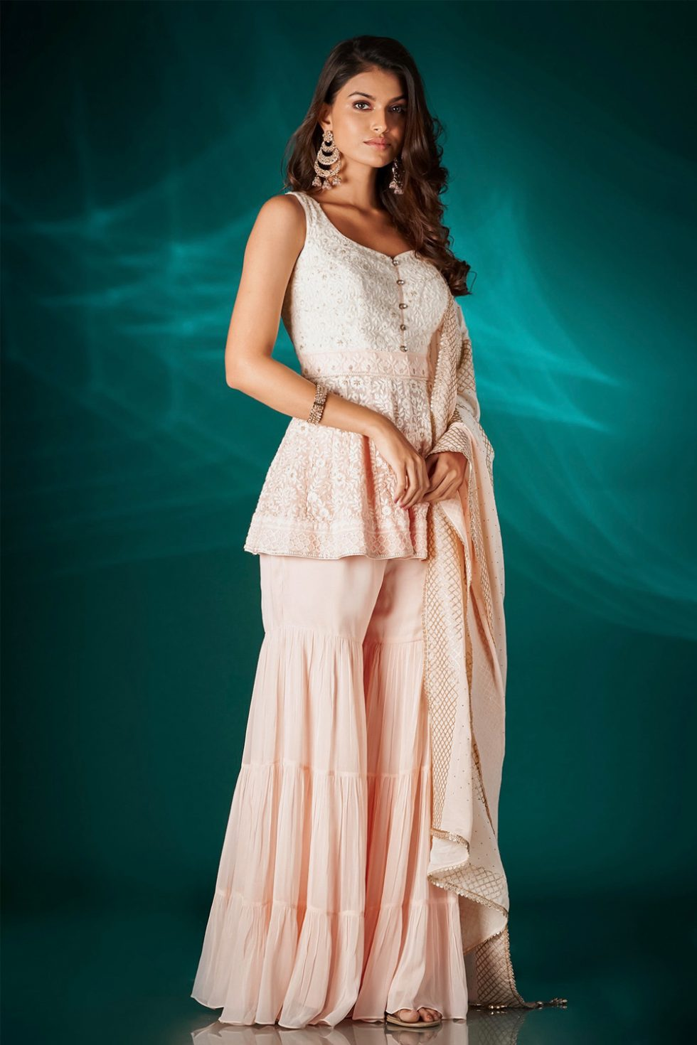 Peachish pink tiered sharara pant set with a chikan peplum top paired with a matching dupatta and gold embellishments.
