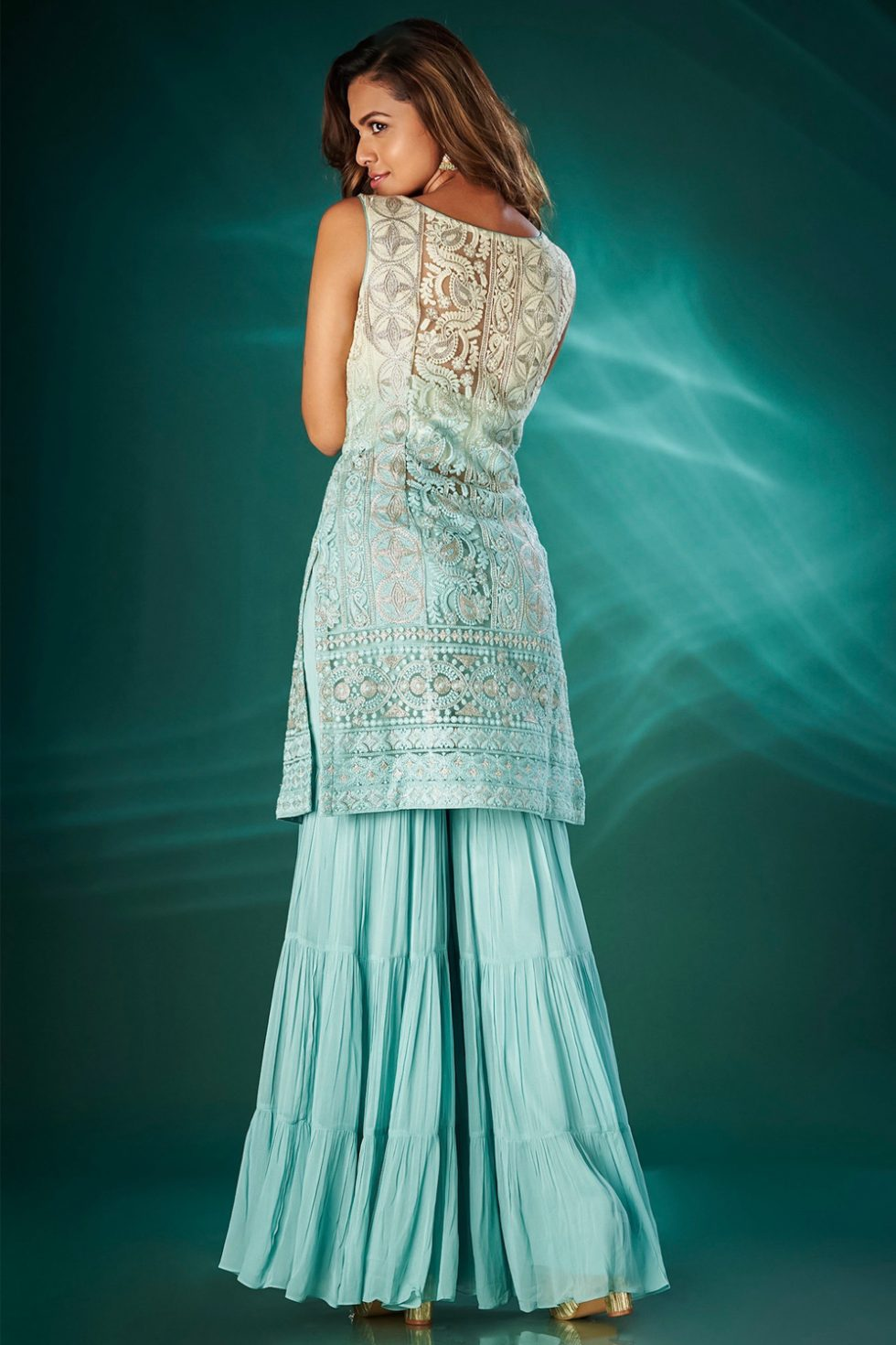 Ivory to sky blue ombré kurta top with a tiered sharara pant paired with a matching dupatta and gold highlights.
