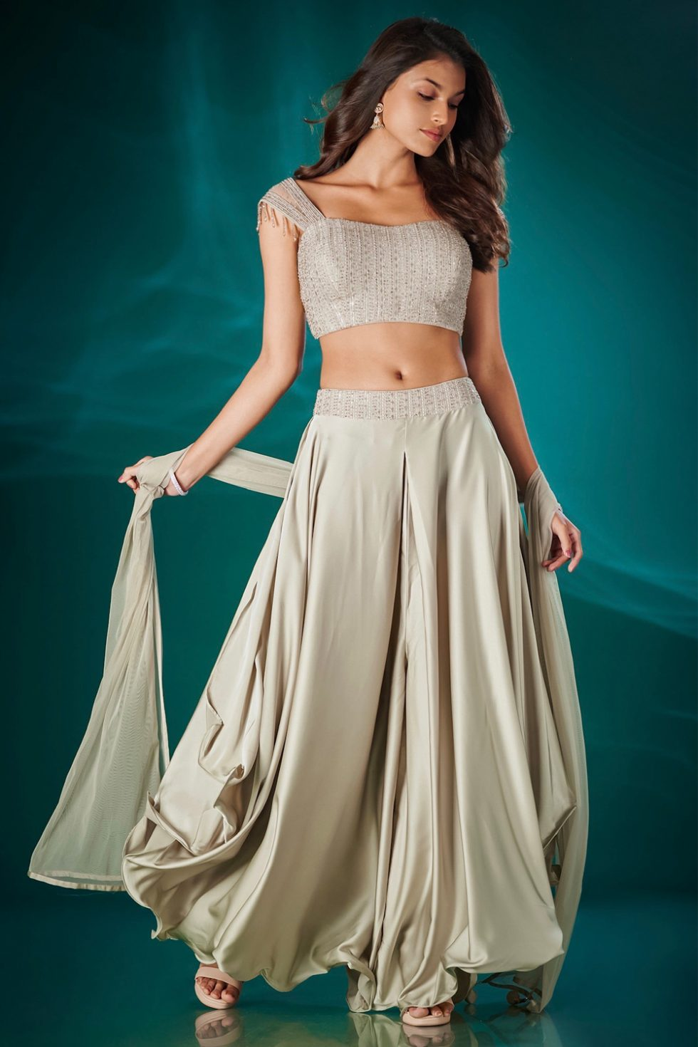 Cream beige draped wide pant set paired with a matching blouse and dupatta with self coloured embellishments and tassels.