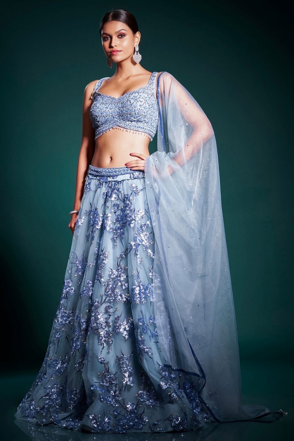 Ocean blue lehenga set with a hand embroidered blouse and a lace sequin work skirt paired with a matching dupatta and tassels