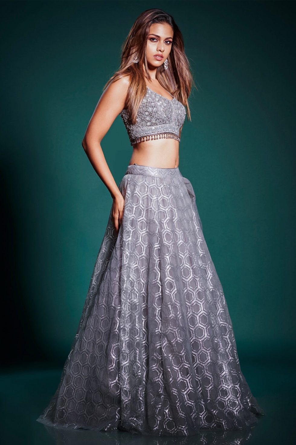 Silver grey lehenga set with a hand embroidered blouse and patterned skirt paired with a matching dupatta and tassels.