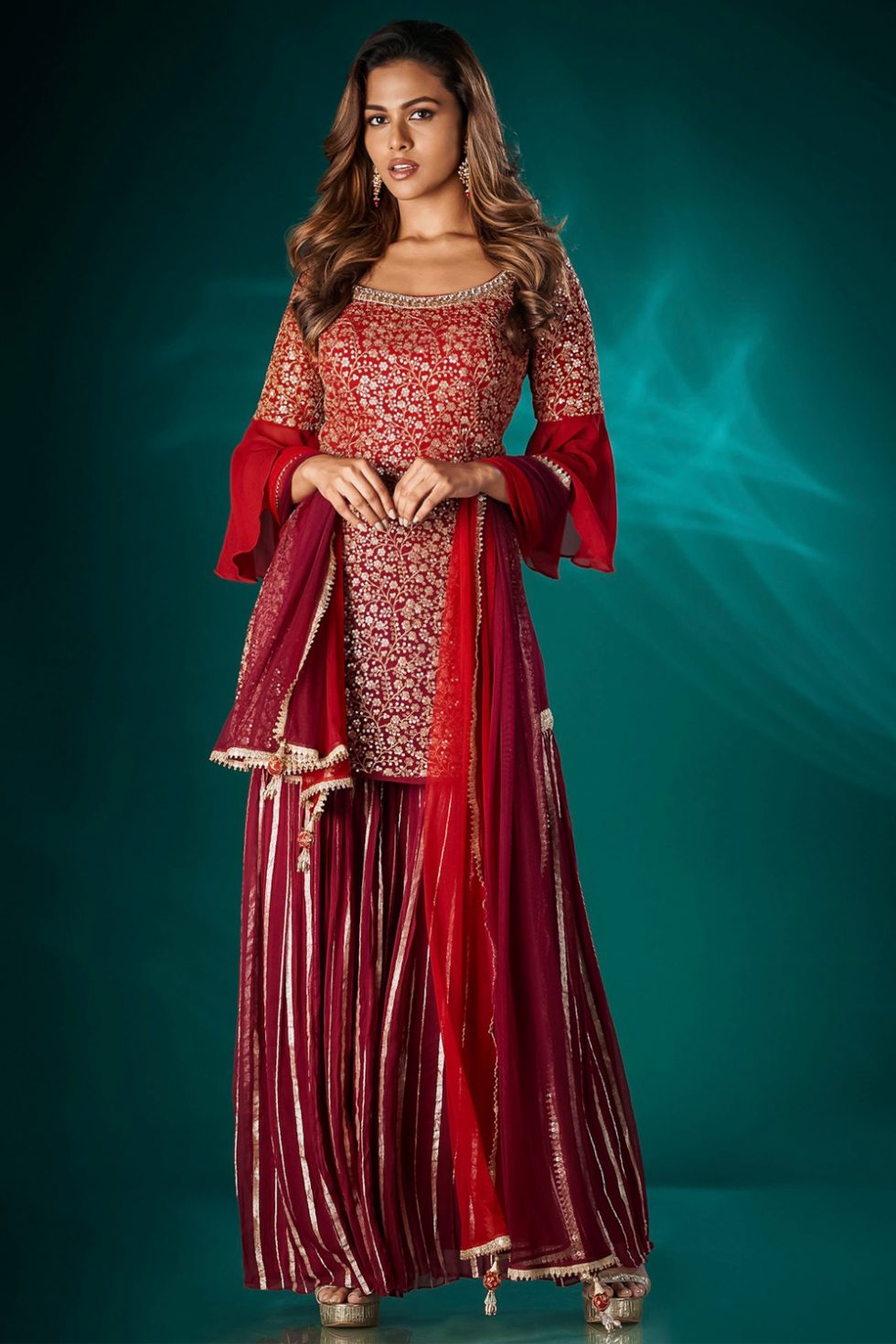 Maroon red chikan kurta top with a single tier patterned sharara pant paired with a matching dupatta and gold embellishments.