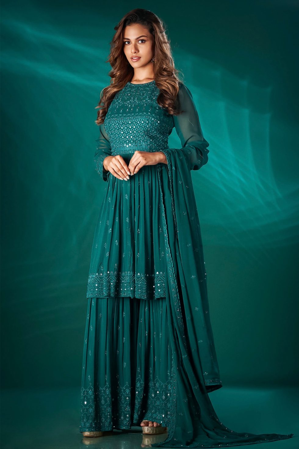 Bottle green single tiered sharara pant set with a peplum style chikan top paired with a matching dupatta and silver highlights.