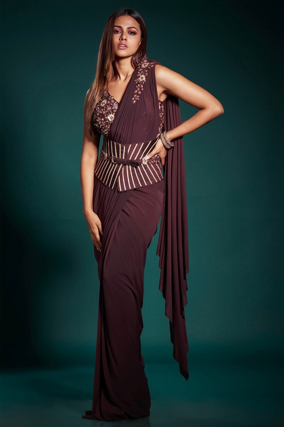 Brick burgundy pre stitched draped saree with a matching embroidered blouse and a wide striped waist belt.