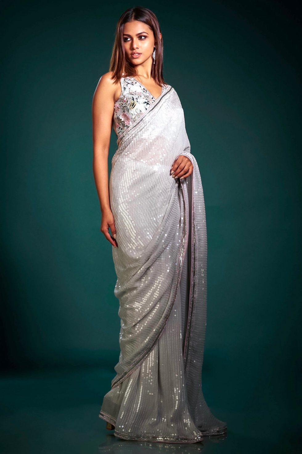 Steel grey classic sequin saree paired with a matching blouse with contrast coloured embroidery and cutwork.