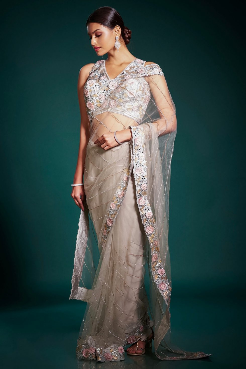 Ash grey classic saree with 3D cutwork and contrast embroidery paired with a matching embroidered blouse and silver and gold details.